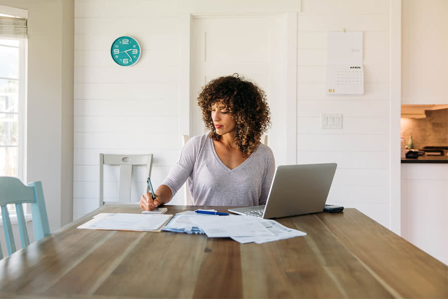 Woman doing her finances at the kitchen table, start a budget concept